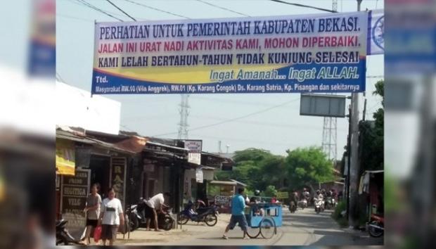 11081 medium warga pasang spanduk protes jalan rusak di kabupaten bekasi