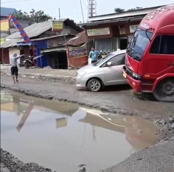 42693 medium kondisi kerusakan jalan raya legok satu lajur terendam air seperti kolam