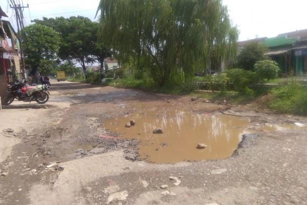 58579 medium jalan utama di perumahan griya asri  sumber jaya  tambun selatan  kabupaten bekasi rusak parah. kerusakan jalan ini bahkan mencapai ratusan meter yang ada di kedua arah.